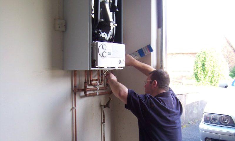 un homme plombier chauffagiste entrain de reparer chaudiere