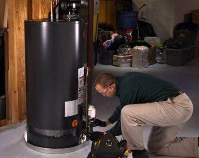 technicien chauffagiste qui dépanne un boiler