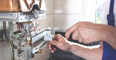 Le chauffagiste répare le système d'allumage du boiler
