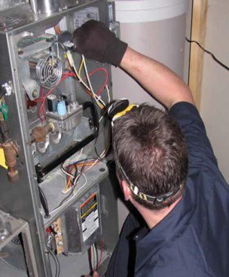 Le chauffagiste répare la chaudière murale