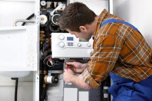 technicien qui répare une chaudière
