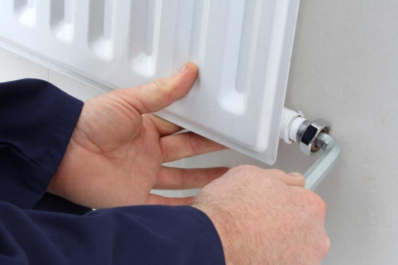 chauffagiste qui purge un radiateur
